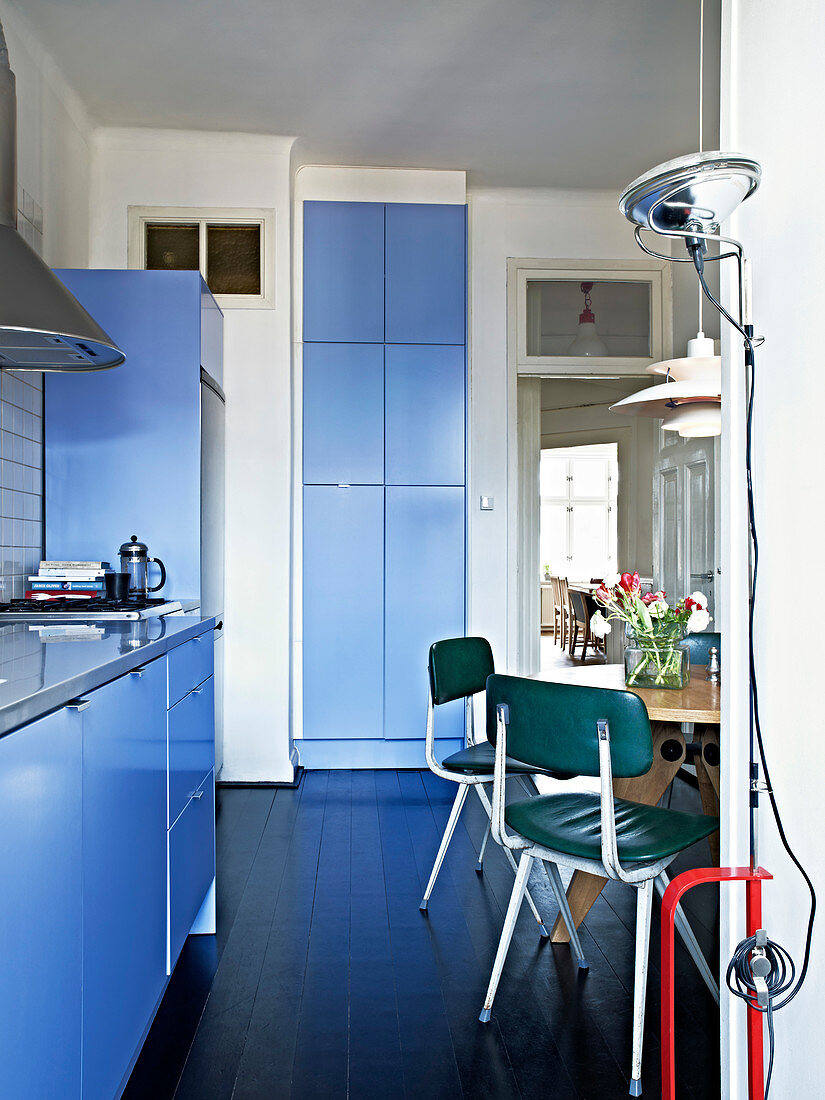 Retro chairs and designer lamps in the dine-in kitchen with blue fronts