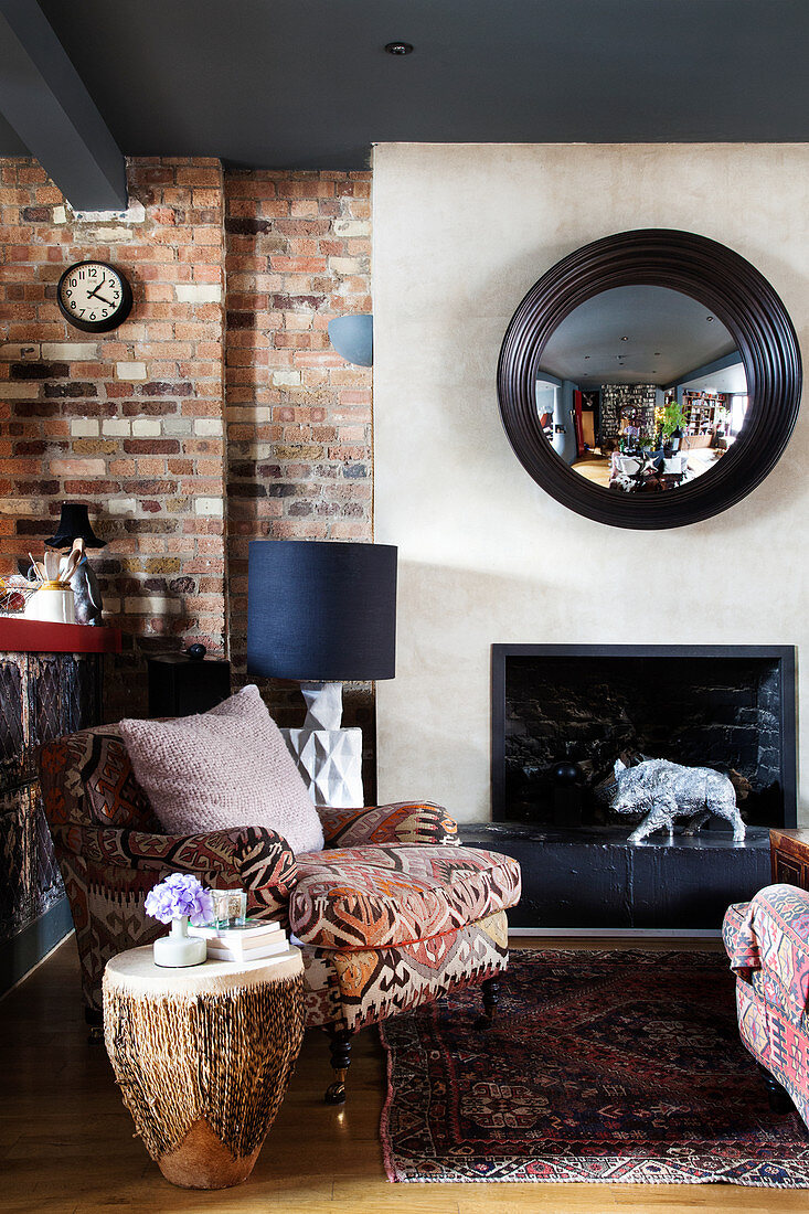 Armchair with ethnic cover an African drum as a side table in front of the fireplace