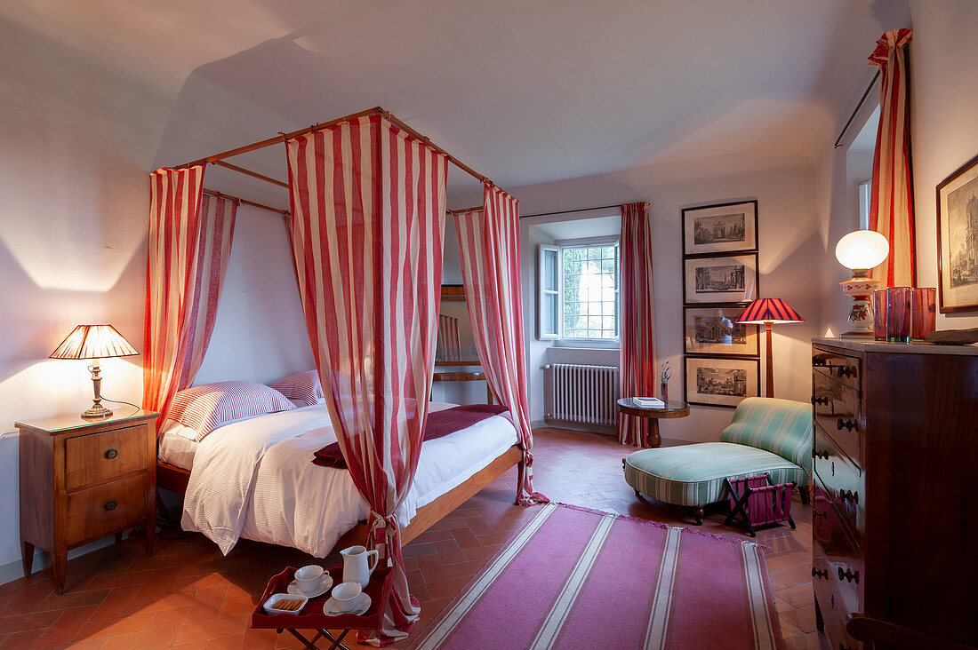 Double bed with red-and-white curtains, antique cabinet and couch in bedroom