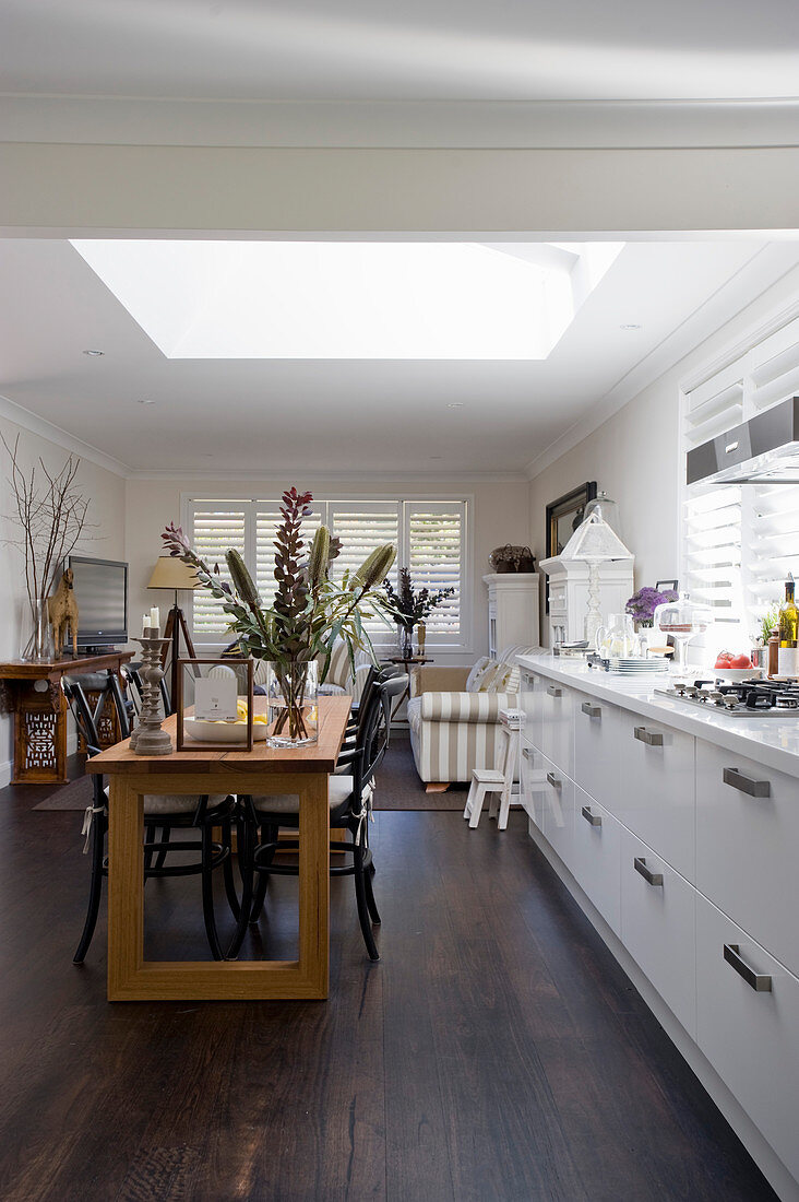 Dining table and open-plan kitchen in long room with skylight