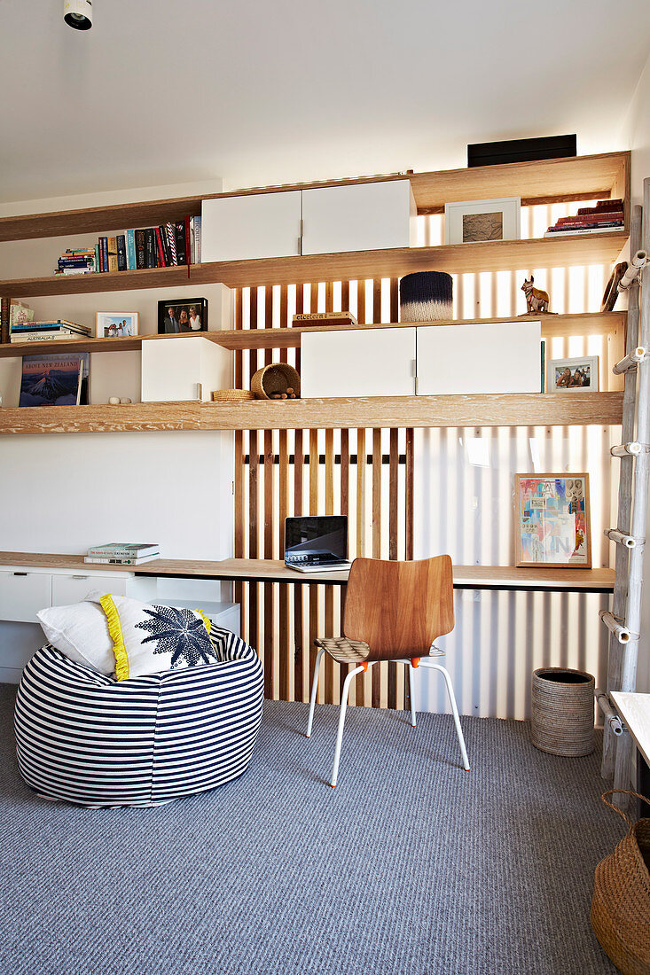 Open shelf above desk and striped beanbag in home office