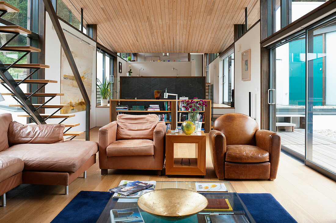 Open-plan interior of 60s, architect-designed house with wooden ceiling and glass walls