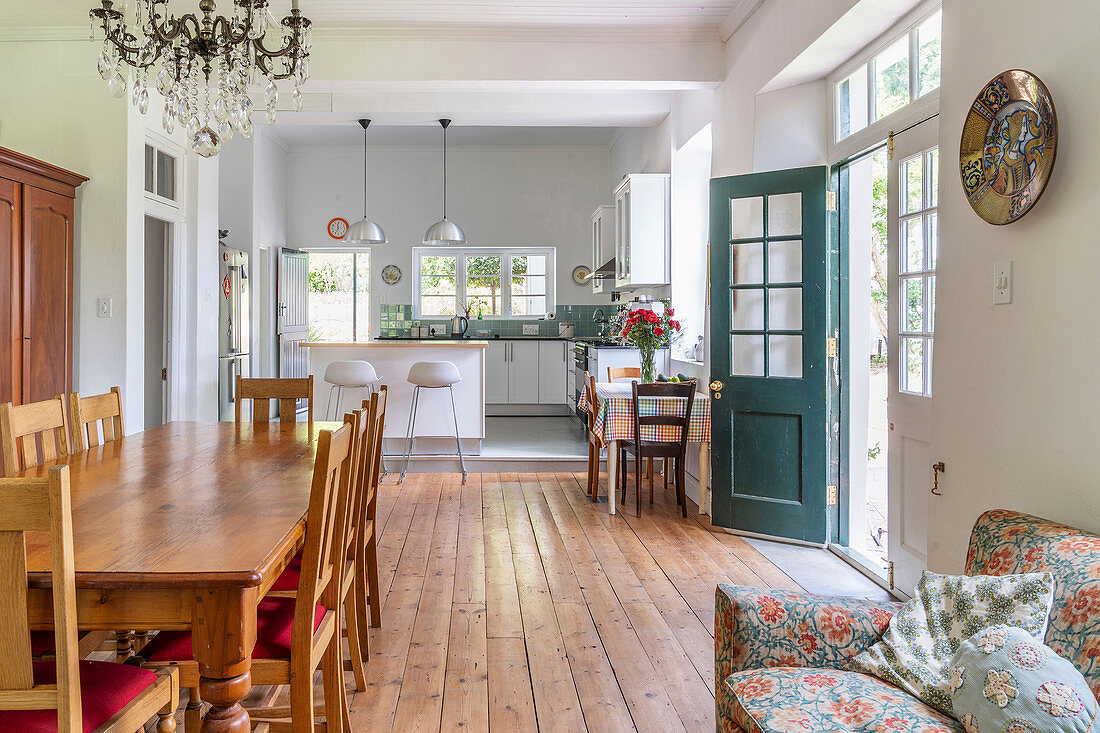 Long wooden dining table and chairs in open-plan interior with wooden floor and kitchen in background