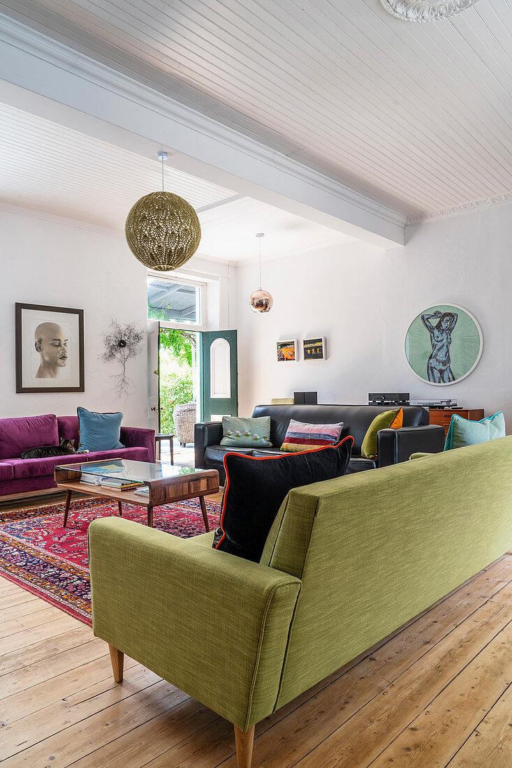 Dark leather, purple velvet and lime-green sofas in living room
