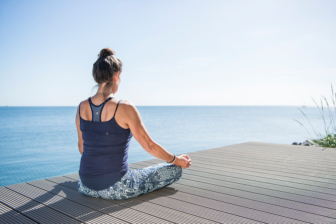 Frau in Meditationssitz am Meer