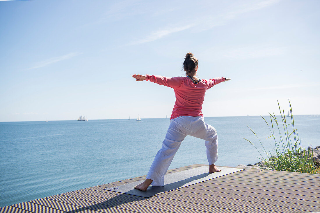 Woman doing yoga on terrace by the sea