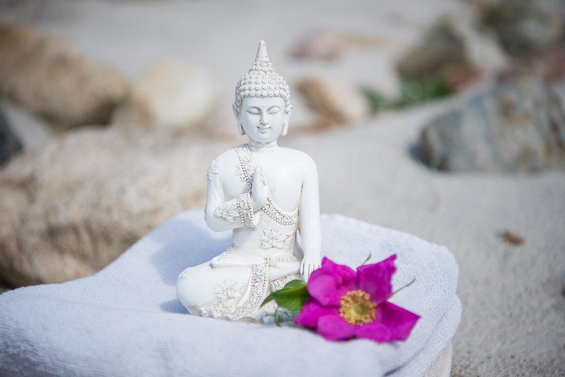 Buddha figurine and flower on towel