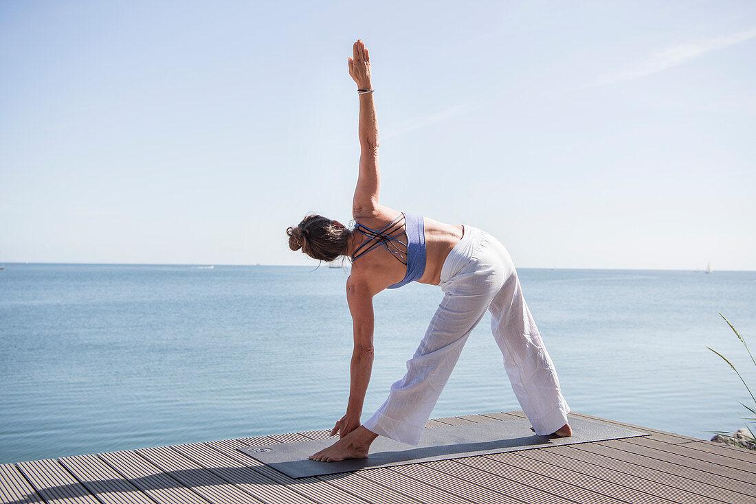 Frau macht Yoga-Übung am Meer