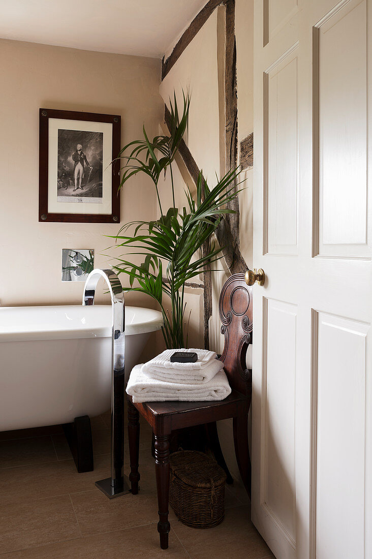 Antique chair next to free-standing bathtub with modern tap fitting against half-timbered wall