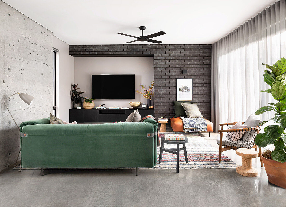 Green velvet sofa in the living room with concrete and brick wall