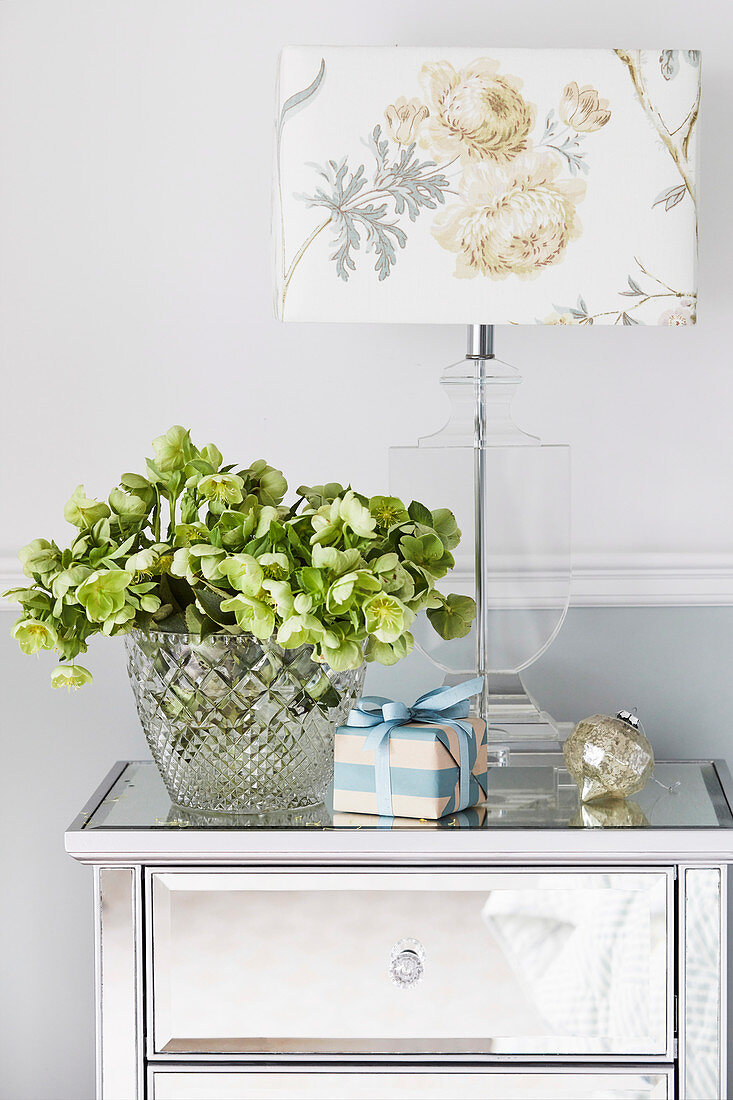 Christmas roses in a glass vase next to a table lamp with a floral motif on a silver bedside table