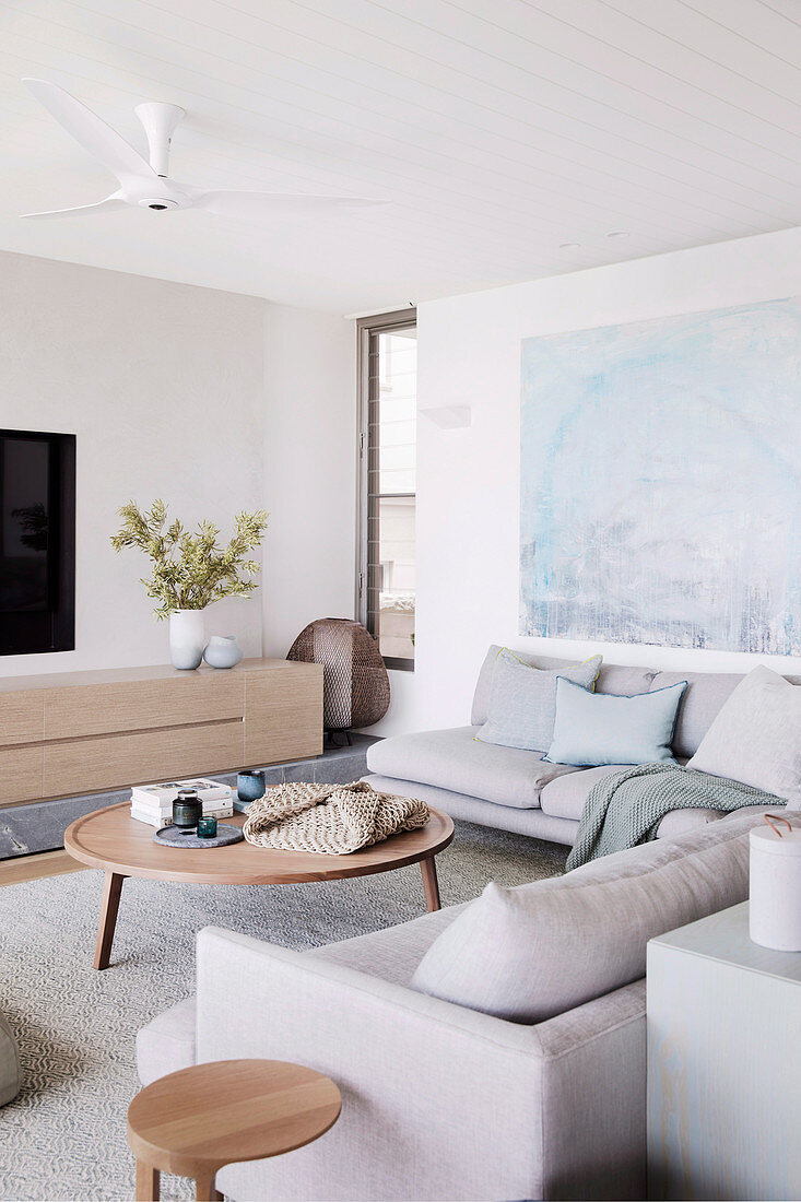Gray corner sofa and wooden furniture in the living room in natural tones