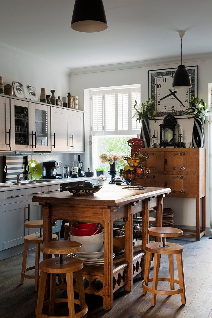 Arts and Crafts altar table used as island counter and Shaker-style cabinets in kitchen