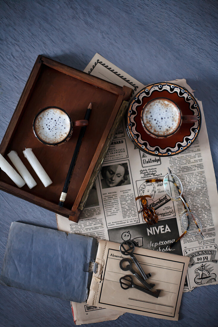 Old newspaper, tray, coffee cups, candles and key