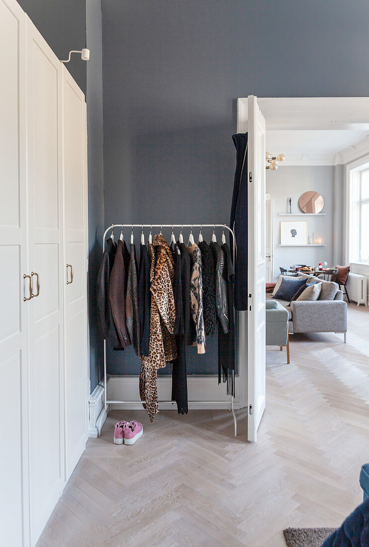 Clothes rail next between white wardrobe and open double doors in period apartment