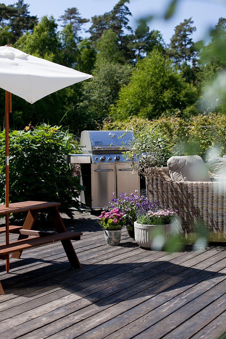 Barbecue, picnic table and wicker sofa on summery terrace