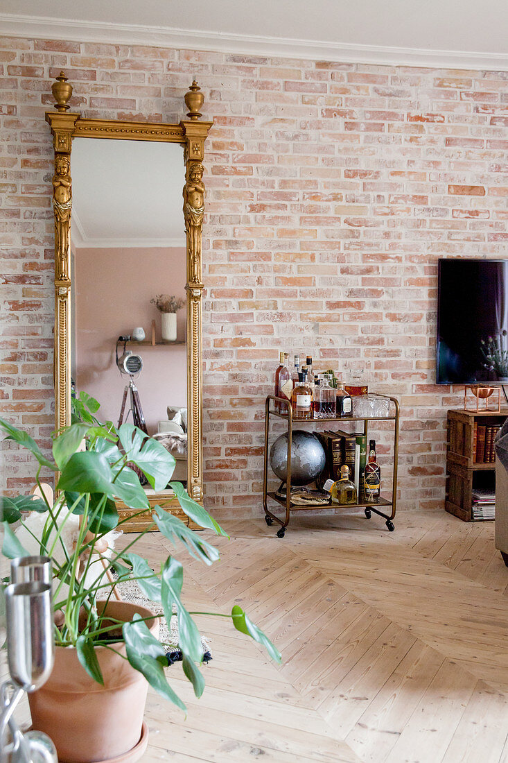 Vintage serving trolley and gilt-framed mirror against brick wall