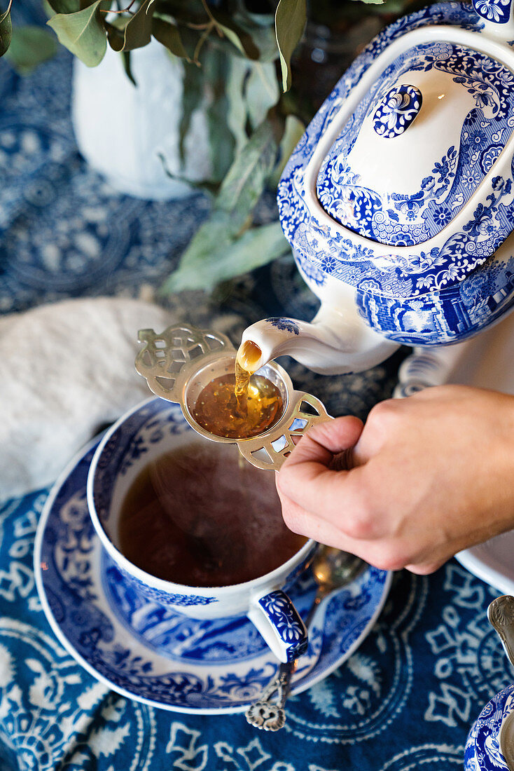 Tea being poured into teacup through antique ta strainer from blue-and-white teapot