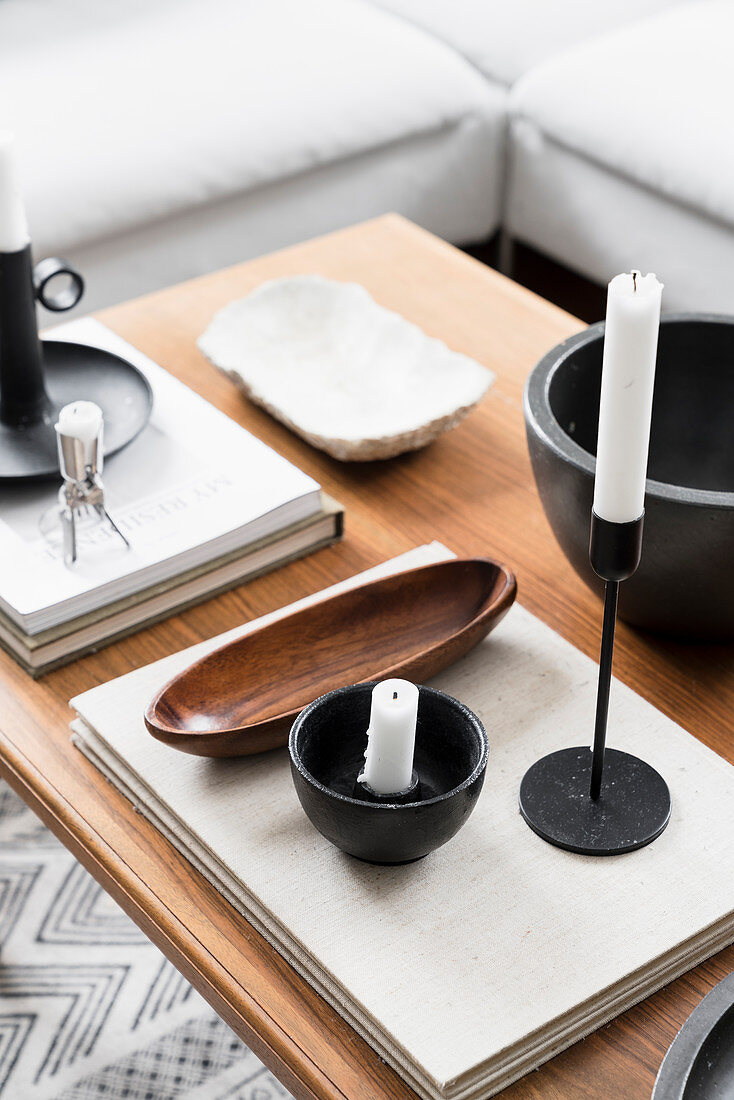 Candlestick, bowls and books on coffee table