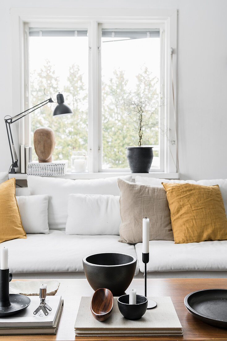 Ornaments on coffee table in front of sofa with mustard-yellow cushions below window