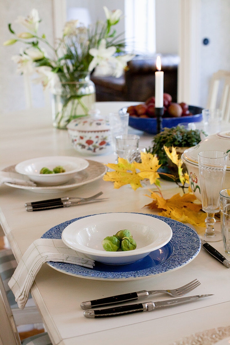 Table set for autumn dinner decorated with leaves