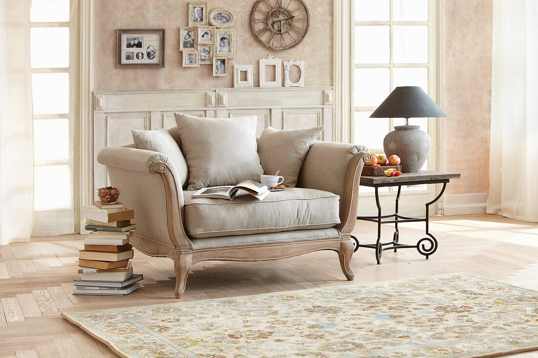 Stacked books next to vintage-style armchair in beige living room