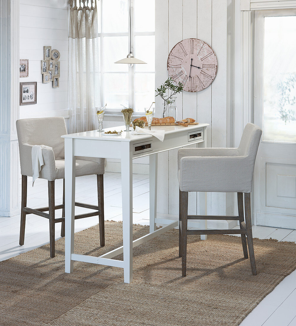 Upholstered bar stools at high table in rustic apartment