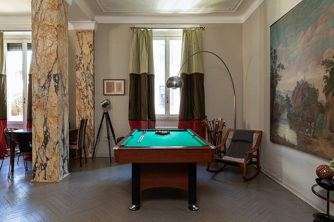 Pool table in open-plan interior with marble pillars