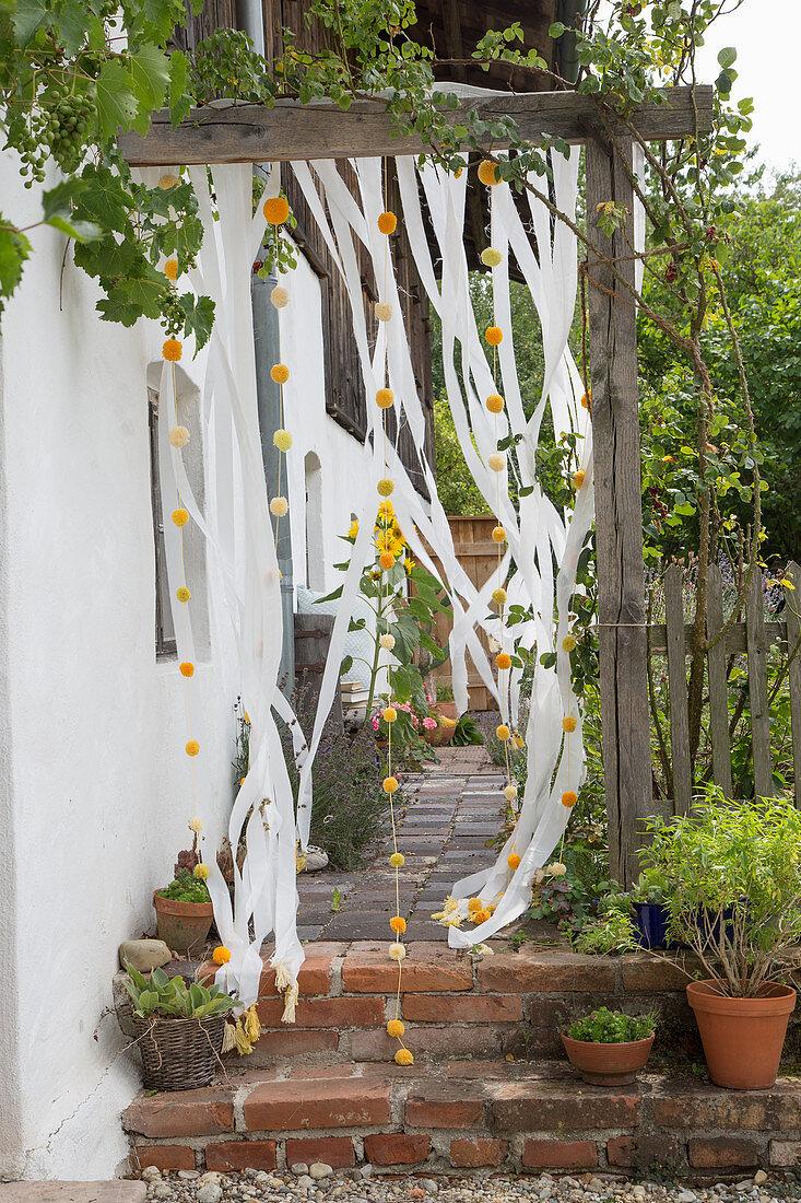 Strip curtain with garland of pompoms on doorway in garden