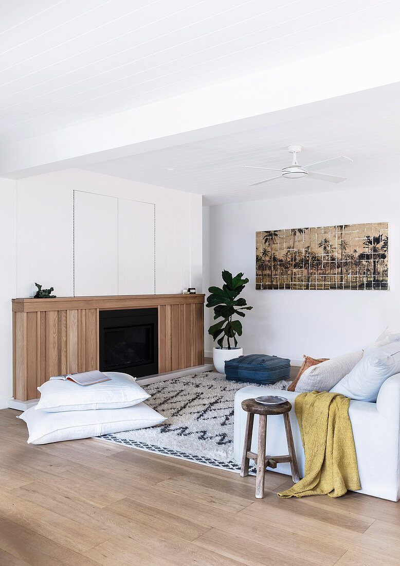 Pillows on carpet in front of fireplace with wood paneling in living room