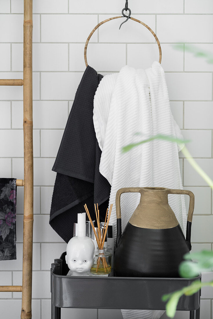Bathroom accessories on black trolley in front of towel ring