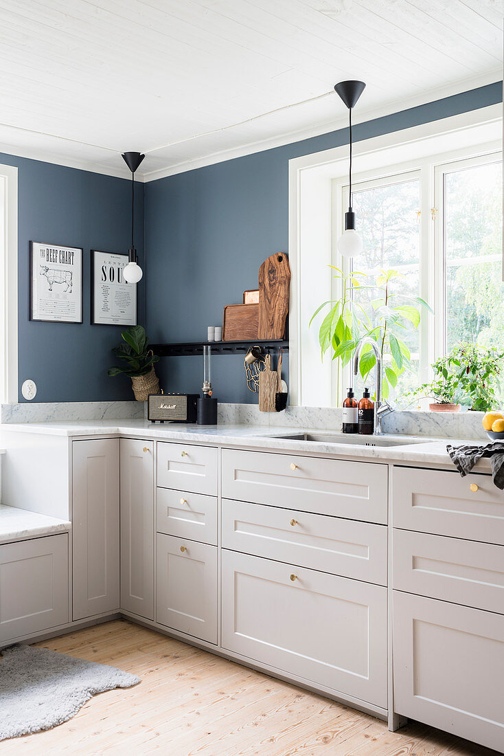 White kitchen counter with marble worksurface below window in kitchen with grey-blue walls