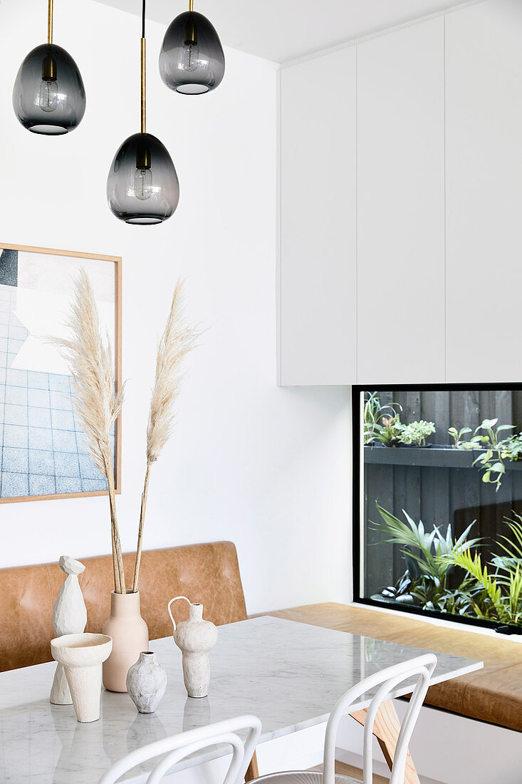 Living room with marble dining table and built-in plant terrarium as wall decoration