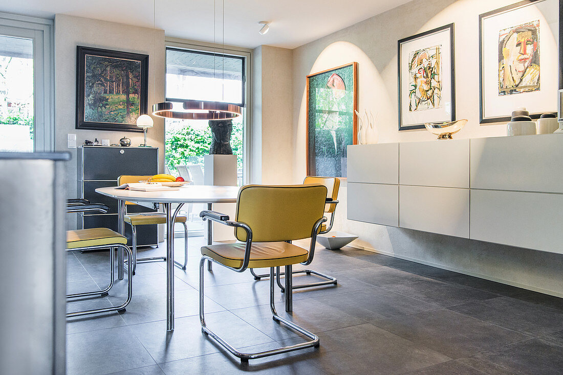 Round table, cantilever chairs, floating sideboard and artworks on wall in open-plan dining area