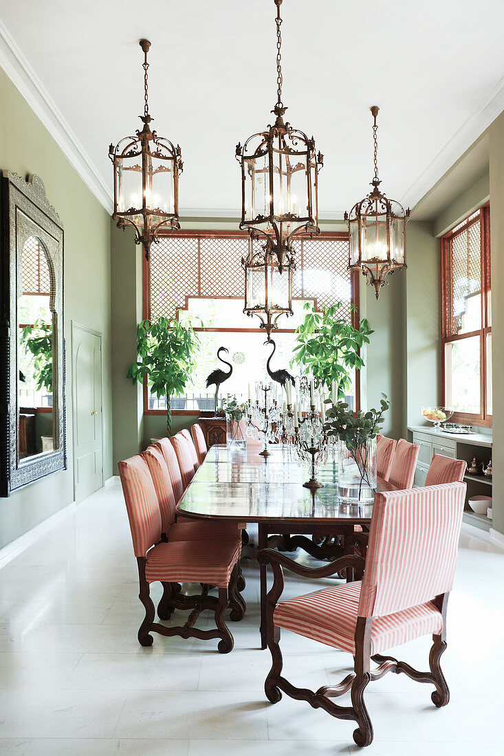 Elegant candlesticks on long dining table and chairs in bright dining room