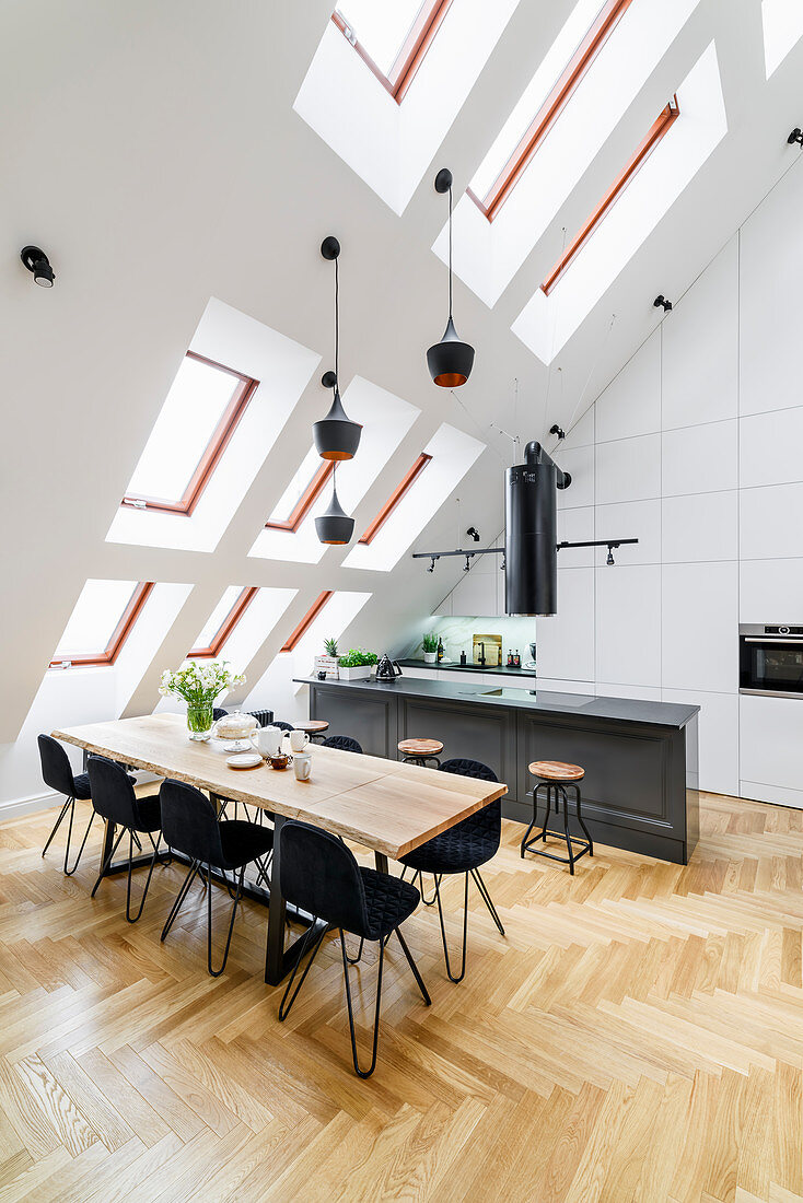 Island counter with bar stools and dining table with black chairs in high-ceilinged room with skylights in sloping wall