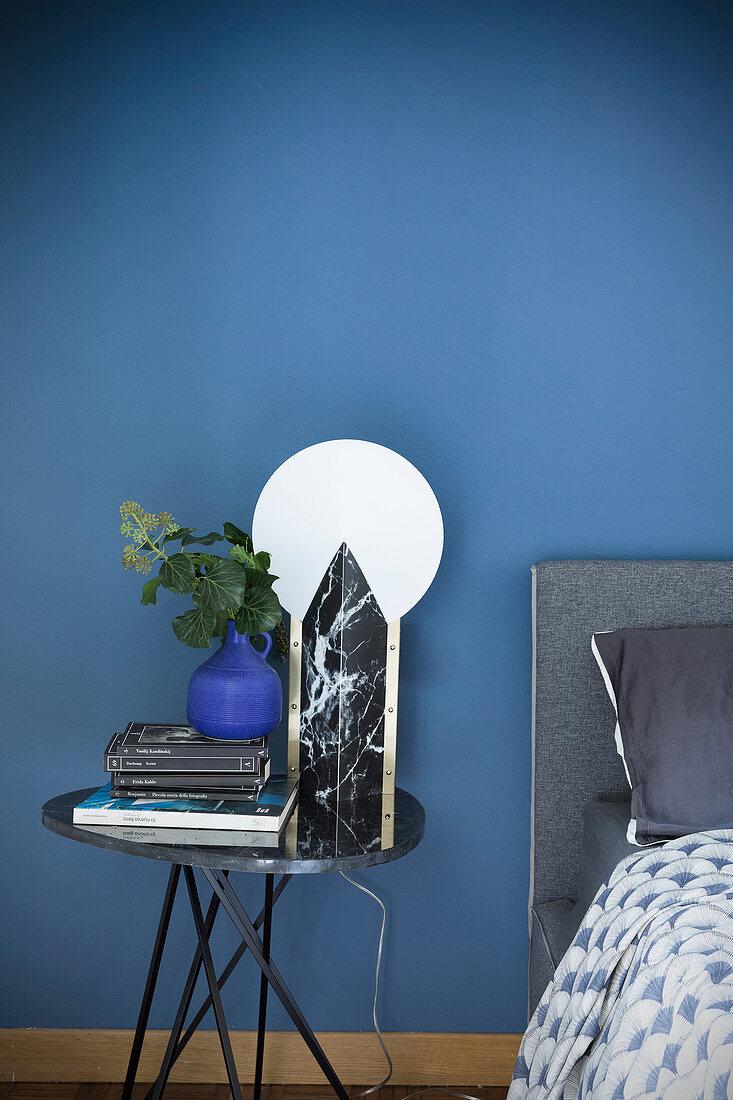 Black marble table lamp against blue bedroom wall