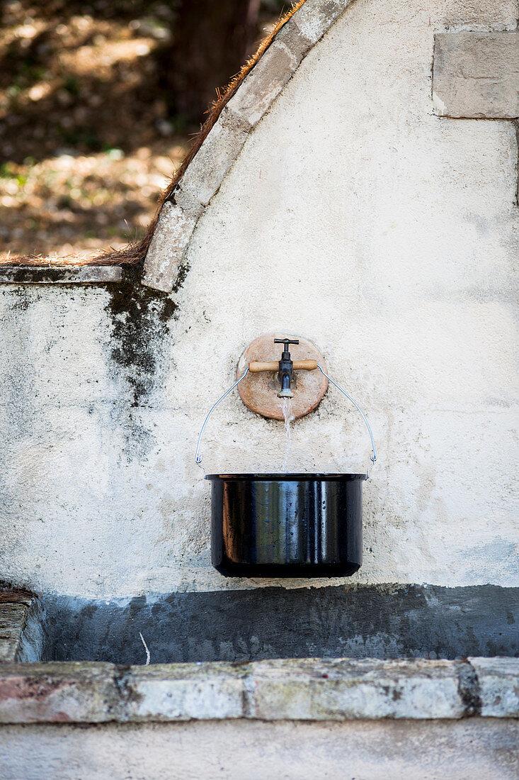 Saucepan below tap of stone fountain