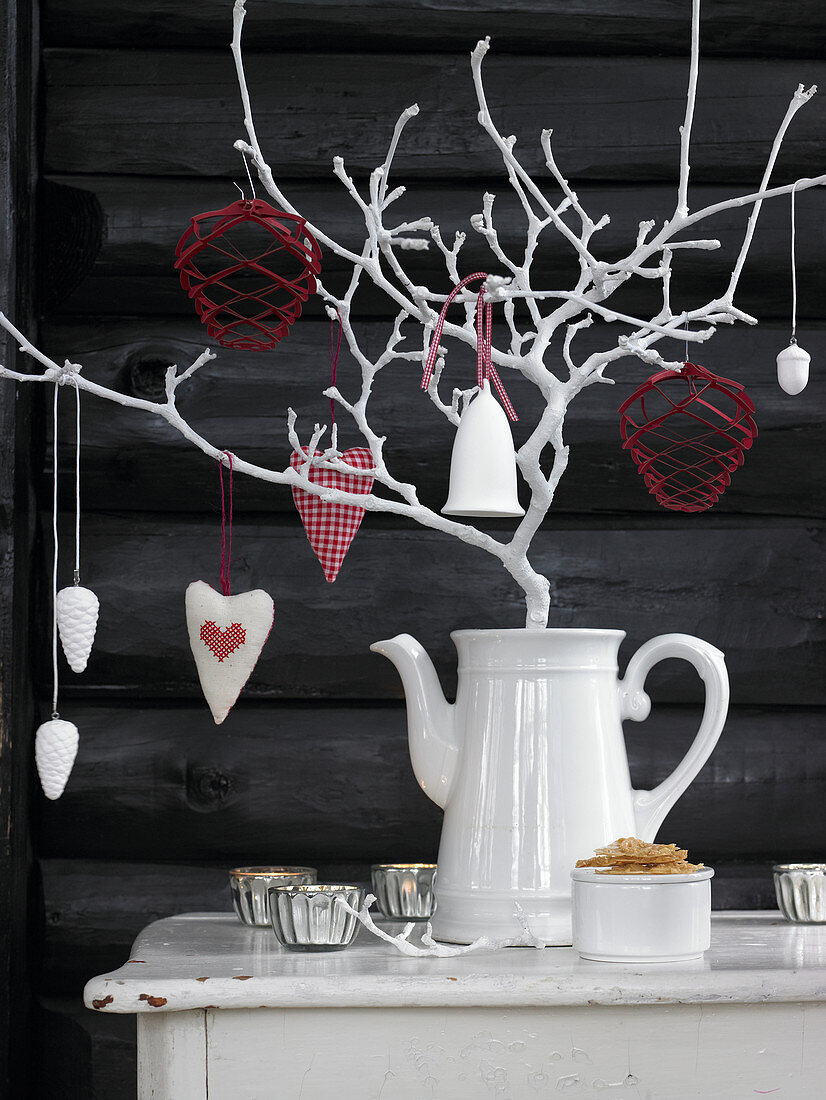 Decorations hung from branch painted white in coffee jug