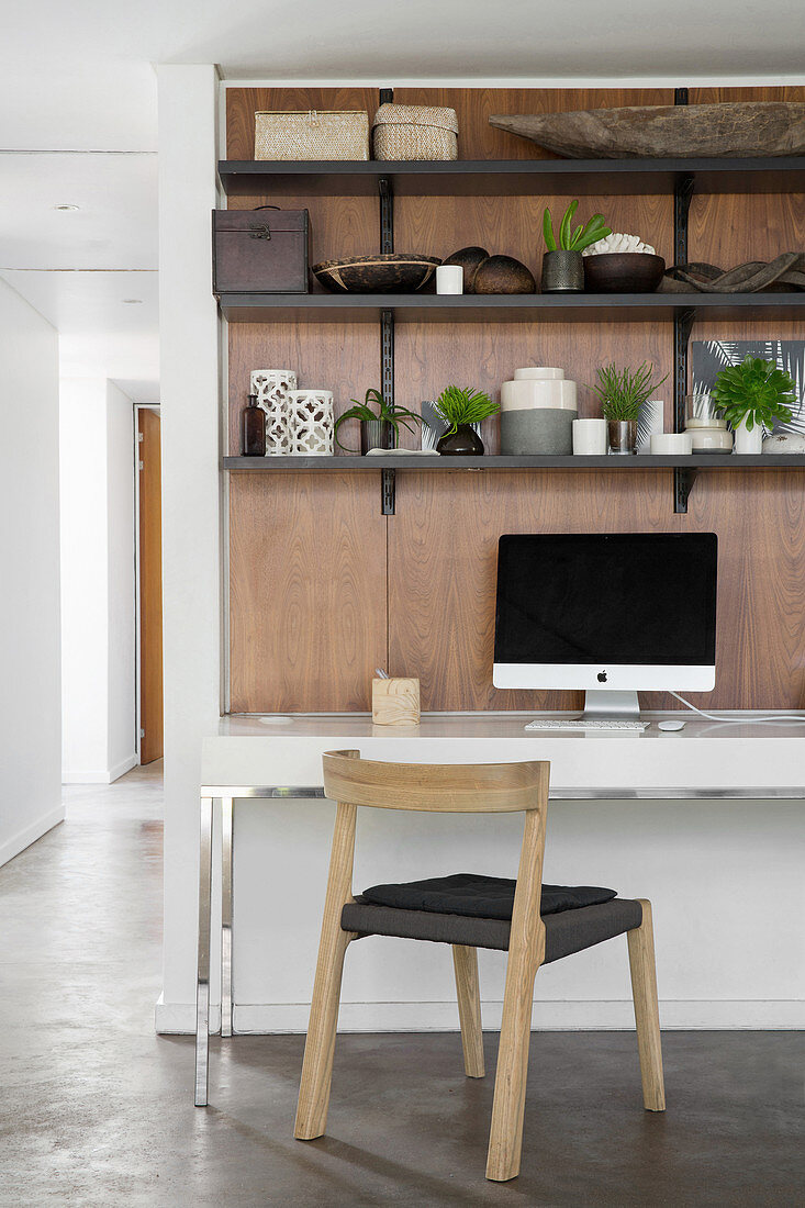 Desk and shelves on wooden wall panel in open-plan interior