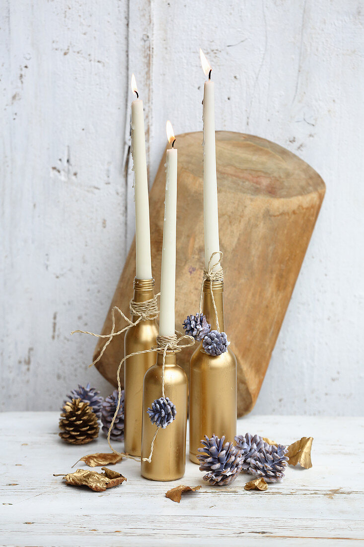 Bottles sprayed gold and used as candlesticks arranged with pine cones and leaves