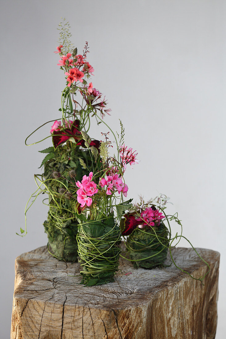 Summer flowers in various vases decoratively wrapped in leaves and grasses
