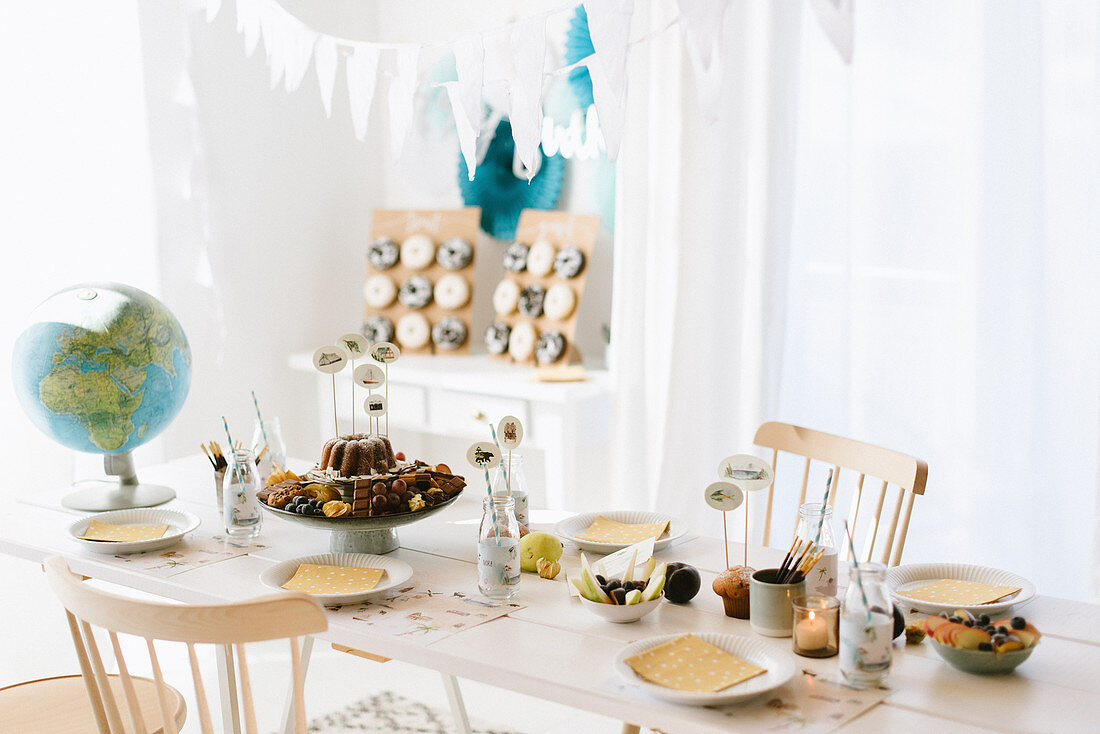 Table set for child's birthday party with world travel motif
