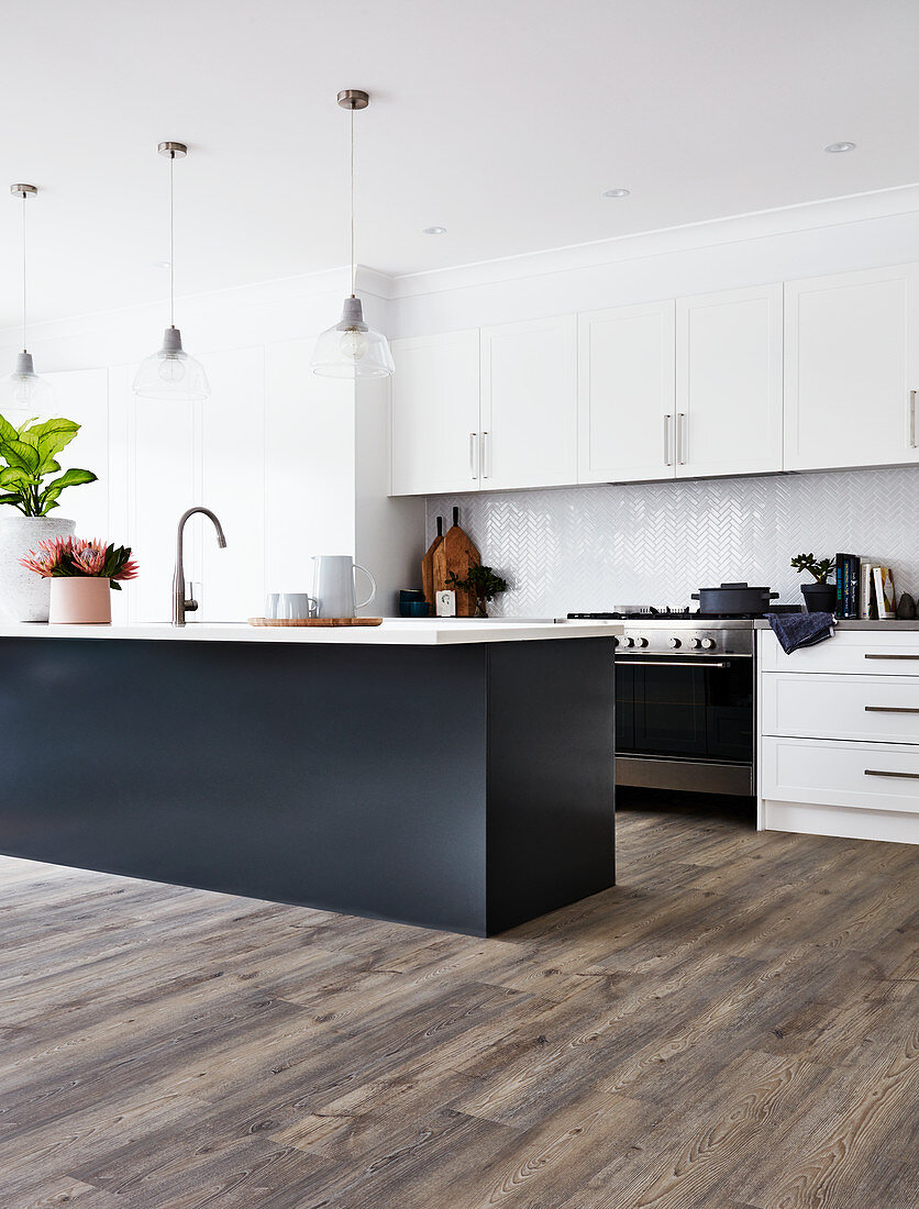 Modern, open-plan kitchen with black island counter and white cupboards