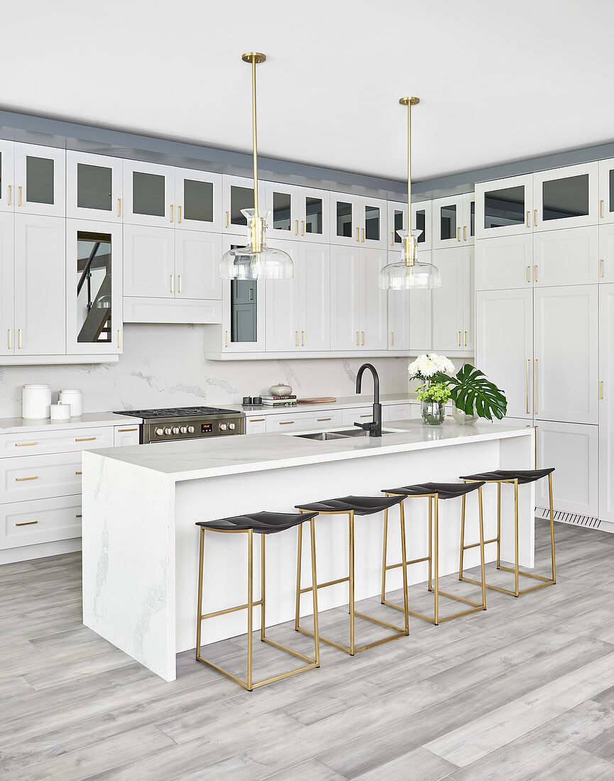 White kitchen with island counter, bar stools and glass and brass pendant lamps