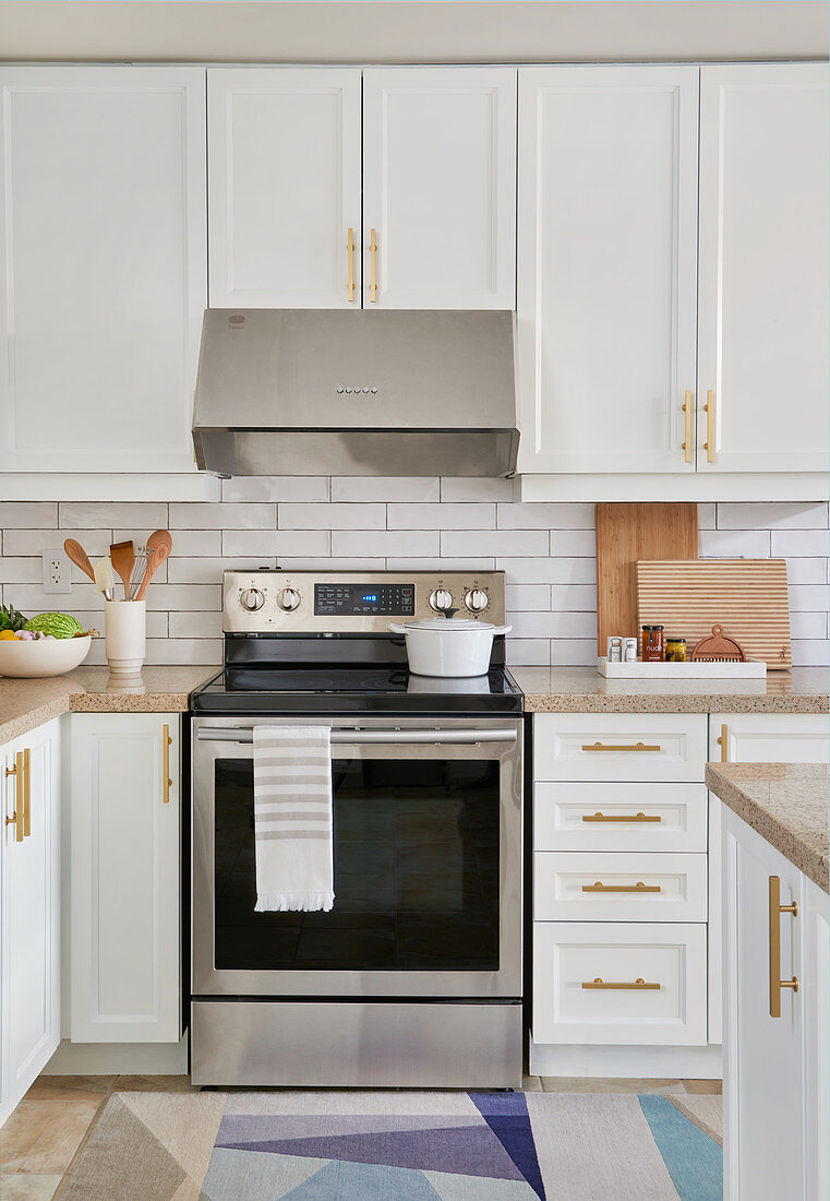 White kitchen with light wood accents, stainless appliances and white subway tiles