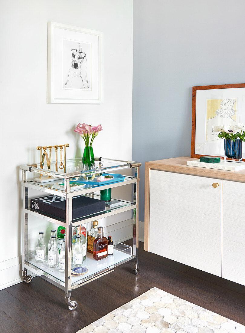 Chrome and glass bar trolley beside sideboard