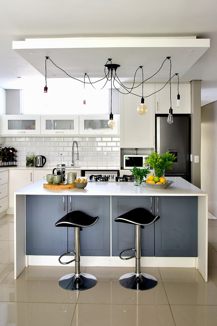 Kitchen counter, bar stools, pendant lamps and shiny tiled floor in open-plan kitchen