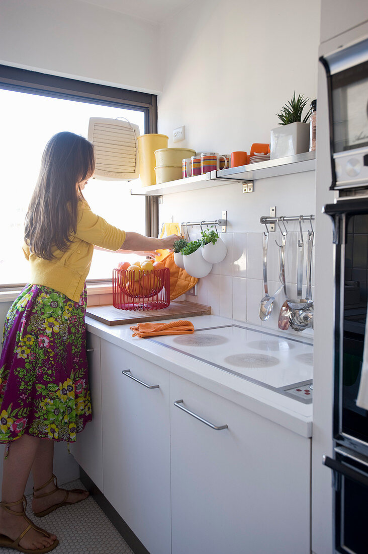 Woman in white fitted kitchen