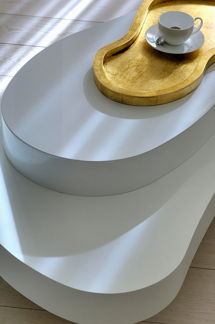 Coffee table with organic shape and cup of coffee on matching tray